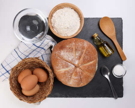 Fresh baked round bread loaf on black slate stone tablet with spoon wheat flower oil water salt kitchen napkin over white background