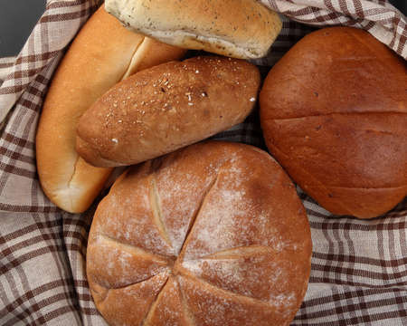 Freshly baked bread loaf bun roll round long mix verity wrapped in checkered kitchen fabric napkin towel wheat flower oil water salt eggs rolling pin slate stone over black background