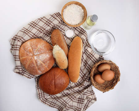 Freshly baked bread loaf bun roll round long mix verity wrapped in checkered kitchen fabric napkin towel wheat flower oil water salt eggs over white background