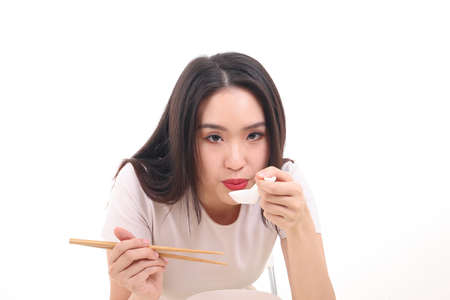 Beautiful young south east Asian woman holding chinese empty chopstick soup spoon bowl utensil pretend acting posing see eat taste feed offer satisfaction yummy white background happy blow cool