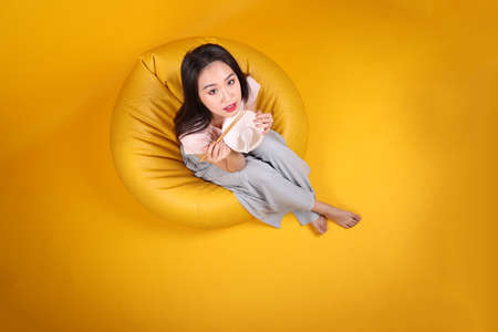 Beautiful young south east Asian woman holding empty chopstick soup spoon bowl posing see eat taste smell feed offer satisfaction yummy siting on beanbag seat yellow orange background top view Reklamní fotografie