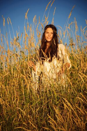downshift: Beautiful hippie girl stands in the grass smiling.