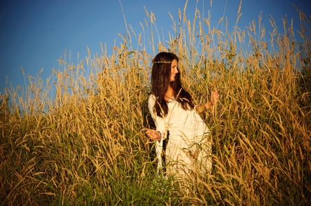 Beautiful hippie girl stands in the grass smiling.