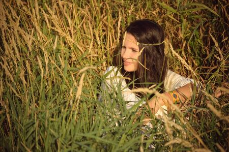 The having a rest hippie girl sits in a grass. Stock Photo
