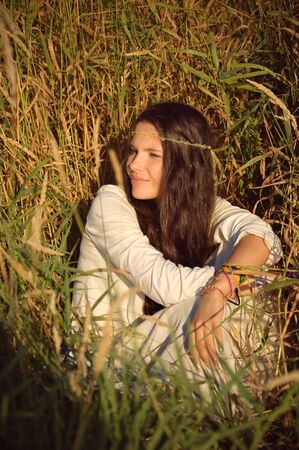 downshift: The having a rest hippie girl sits in a grass. Stock Photo