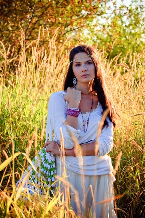 Beautiful hippie girl in the tall grass