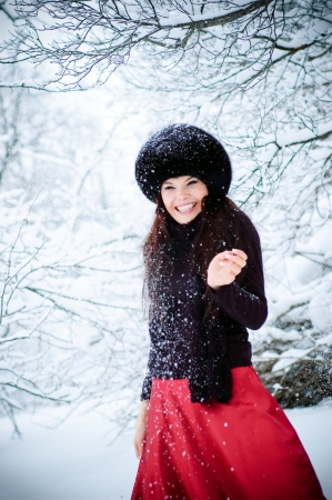 The laughing woman stands under falling snow. Stock Photo