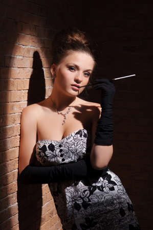 Elegant beautiful woman holds cigarette and looks at camera.
