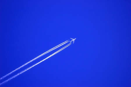Jet plane at high altitude in the deep blue sky.