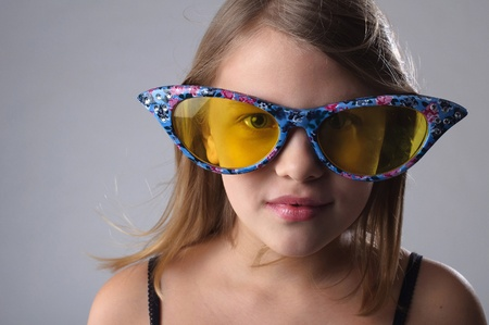 Little girl in funny big glasses in studio. Stock Photo