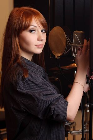Girl in a studio will singing to the microphone.