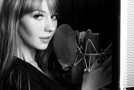 estudio de grabacion: Chica cantando con el micr�fono en un estudio Foto de archivo