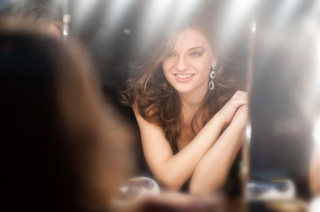 beautiful girl looking through the mirror in dressing room photo