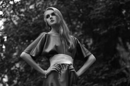Retro vrouw in lange jurk in het park Stockfoto