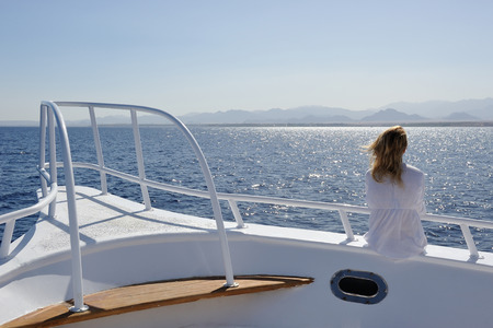 Girl in white on the yacht deck. photo