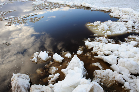 thawing: Thawing of ice with reflection of sky in water. Stock Photo