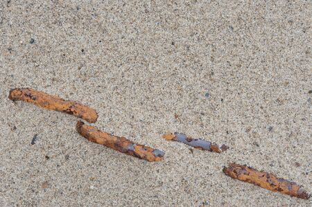 rusty chain: Rusty chain disappears under the sand of the beach Stock Photo