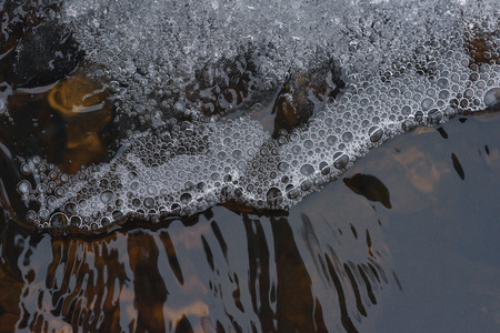 The accumulation of air bubbles under the thin crust of ice against the background of a turbulent flow of water. 版權商用圖片