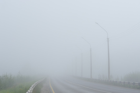 An empty road disappearing into the dense morning fog.