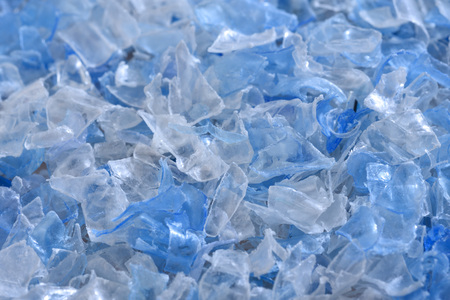 Flakes of crushed plastic bottles as raw material for further processing. Stockfoto
