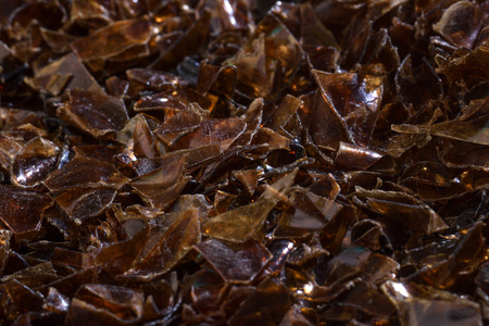 Flakes of crushed plastic bottles as raw material for further processing. Stock Photo