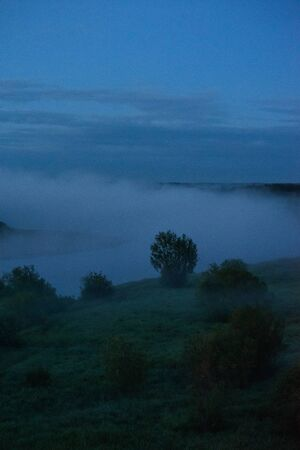 Midnight fog covers the fields and the river and the power lines.