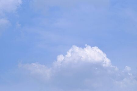 White fluffy clouds against blue sky in bright day for background texture