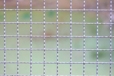 Close up many grid pattern of metal fence with blurred green color for background texture