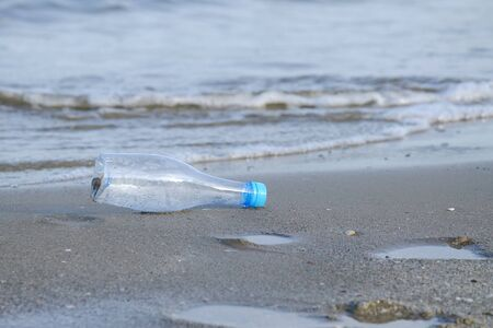 A plastic bottle of drinking water littering on the beach with sea waves background for an environmental cleaning concept