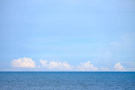 Deep blue sea with a row island in the horizontal line and blue sky white fluffy clouds in bright day