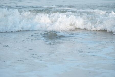 Close up clean white bubble waves at the beautiful beach for background texture