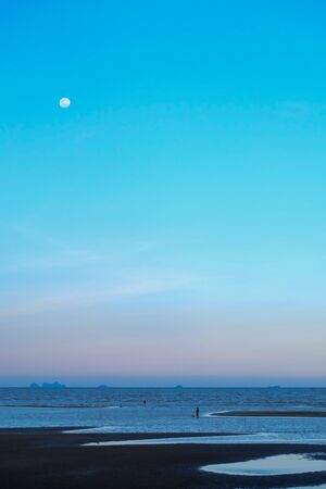 When the moon hits the blue sky with seascape in lately evening and blurred a people walking on the sand beach,velvet color style