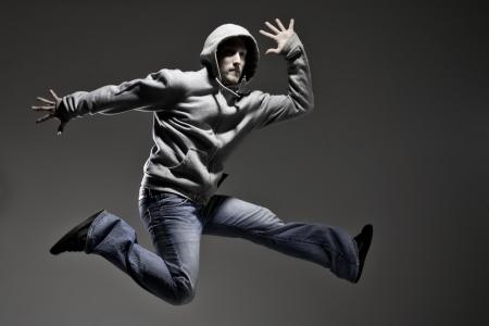 sudadera: Hombre joven que hace un salto sobre fondo gris Foto de archivo