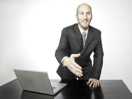 regards: businessman closing a contract in front of your desktop