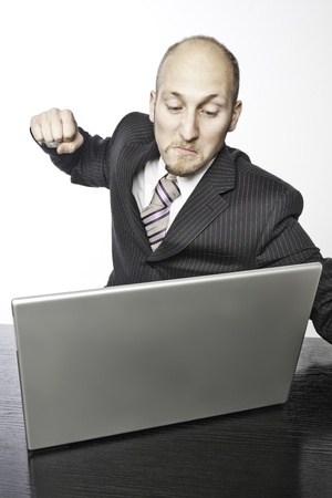 businessman angry at his computer and ready to give it a punch photo