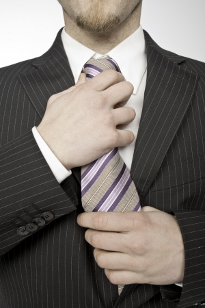 businessman taking the tie knot on white background photo