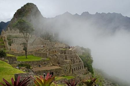 invading: Clouds invading the Inca ruins at Machu Picchu, Peru