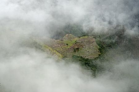 The Inca village of Macchu Picchu seen from the Sun Gate through a hole in the clouds