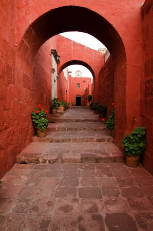 catalina: Red painted walls, arches and flying buttresses line an alleyway through the Santa Catalina Monastery in Arequipa, Peru Stock Photo