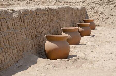 ollas de barro: Las ollas de barro se alinean frente a una pared en la parte superior de la pirámide de barro de la Huaca Pucllana, Lima, Miraflores, Perú