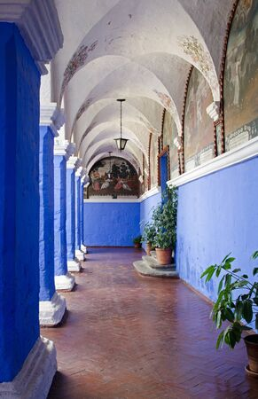 Arcade with blue and white columns in the Orange Tree Cloister of the Santa Catalina Monastery in Arequipa, Peru Фото со стока