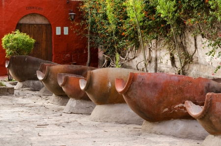 open air: The open air laundry  lavanderia  in Santa Catalina Monastery, Arequipa, Peru  A stone duct delivers water to troughs made of split amphorae   Stock Photo