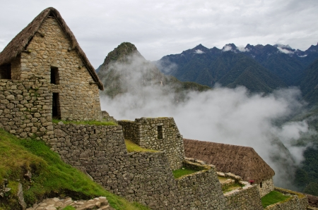 thatched: Cabins with thatched roofs at the entrance to the Imca village Machu Picchu with clouds obscuring the the mountains in the background