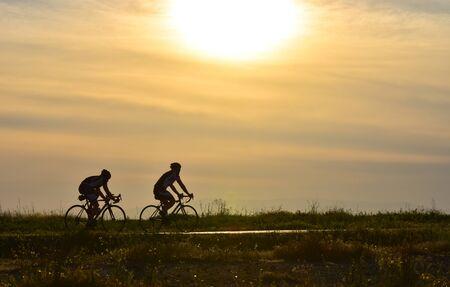 silueta ciclista: Dos ciclistas que montan la bicicleta en el cielo de la puesta del sol, silueta.