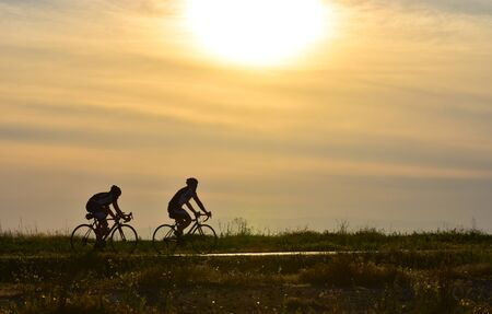 bicycle silhouette: Two cyclists riding bicycle on sunset sky, silhouette. Stock Photo