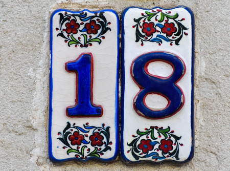 eighteen: House number eighteen. House Number 18 sign on wall.