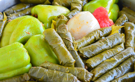 Wrapping and filling - Traditional Turkish food. Pepper and grape leaves stuffed with rice and minced meat.