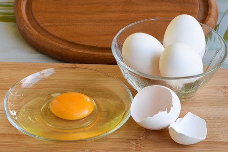 White eggs and a cracked egg. Egg yolk in a plate.