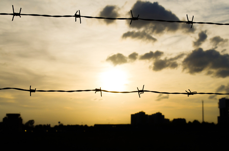 City silhouette and sunset sky with black clouds behind wire mesh.