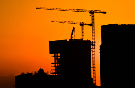 Silhouette of building under construction and the construction crane crane at sunset time or power.